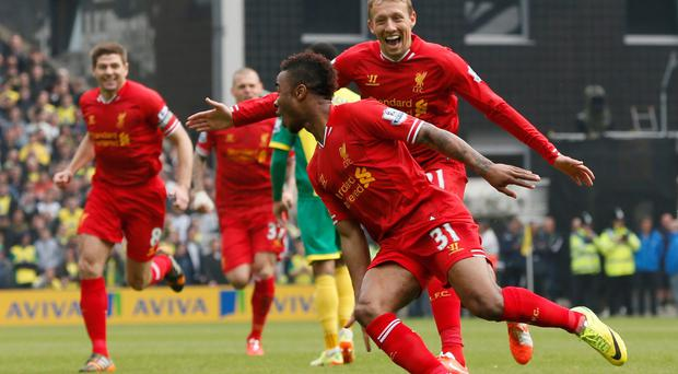 Liverpool's Raheem Sterling (C) celebrates his goal against Norwich City with teammates Lucas Leiva (R) and Steven Gerrard (L)