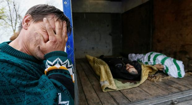 A local resident reacts after looking at the bodies of victims of a gunfight overnight near the city of Slaviansk, April 20, 2014.