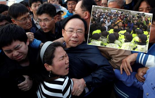 South Korean Minister of Oceans and Fisheries Lee Ju-young (C) struggles with angry family members of the missing passengers who were on the capsized Sewol passenger ship, which sank in the sea off Jindo, during his visit to a port where the family members have gathered, in Jindo April 20, 2014. South Korean prosecutors investigating last week's ferry disaster said on Sunday they wanted to extend the detention of the captain and two other crew by 10 days as they try to determine the cause of the accident that likely claimed more than 300 lives. REUTERS/Kim Hong-Ji (SOUTH KOREA - Tags: DISASTER MARITIME POLITICS TPX IMAGES OF THE DAY)