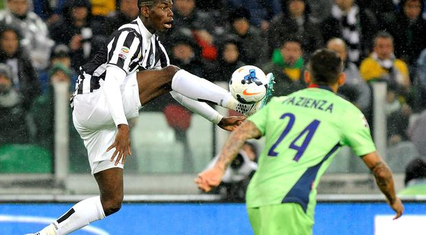 Juventus' Paul Pogba (L) fights for the ball with Bologna's Michele Pazienza