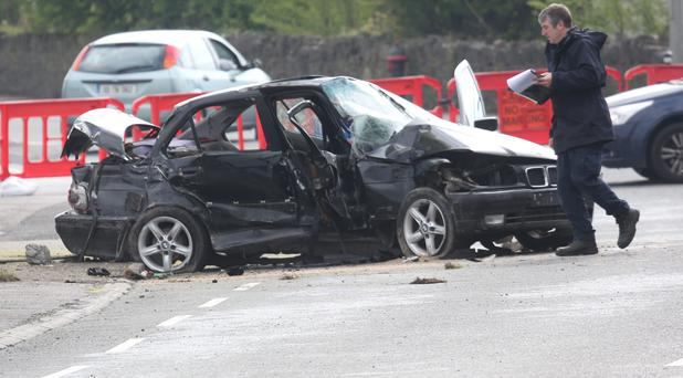 Gardai examine the scene in Roscrea where a black BMW hit a wall killing the driver and injuring one other passenger on the Birr road in Roscrea, Co. Tipperary