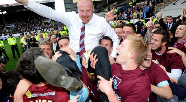 Burnley's manager Sean Dyche (top) celebrates with his players after his side win promtion to the Premier League during the Sky Bet Championship match at Turf Moor