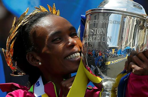 Kenya's Rita Jeptoo holds the trophy after winning the women's division at the 118th running of the Boston Marathon. Photo: Reuters/Brian Snyder