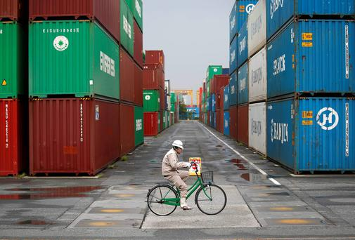 A worker rides a bicycle in a container area at a port in Tokyo. Japan suffered its worst annual trade deficit in March as exports growth slowed to its weakest in a year, suggesting a rapid loss of economic momentum that may prompt policy makers into early action as a national sales tax hike puts more strain on growth. REUTERS/Toru Hanai