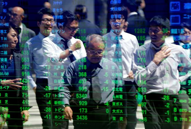Passers-by are reflected in an electronic stock quotation board outside a brokerage in Tokyo April 11, 2014. Japanese shares tumbled to six-month lows on Friday and could log their worst performance since the March 2011 tsunami and nuclear disaster after a rout in U.S. tech shares spurred selling by momentum players. REUTERS/Issei Kato (JAPAN - Tags: BUSINESS)
