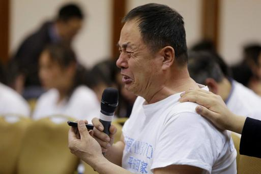 A father whose son was aboard Malaysia Airlines flight MH370, cries as he asks a question during a briefing given by Malaysian representatives at Lido Hotel in Beijing