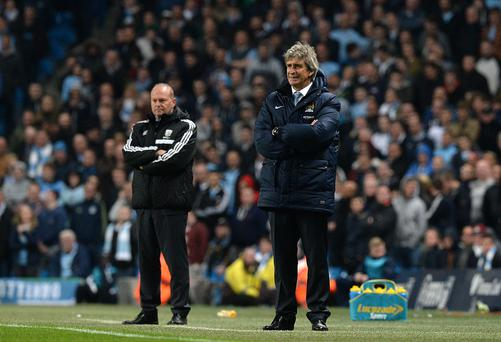 Manchester City manager Manuel Pellegrini and West Bromwich Albion manager Pepe Mel (left) watch from the touchline during the Barclays Premier League match at the Etihad Stadium, Manchester. Photo: Martin Rickett/PA Wire.