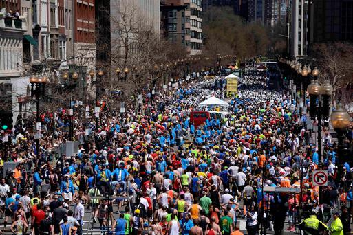 Runners make their way down Boylston Street after finishing the Boston Marathon