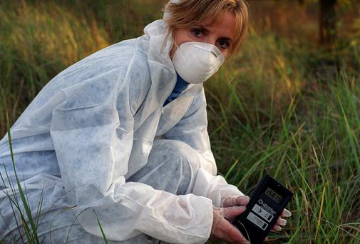 Adi Roche holds a Geiger counter in the exclusion zone, close to the Chernobyl nuclear power plant.