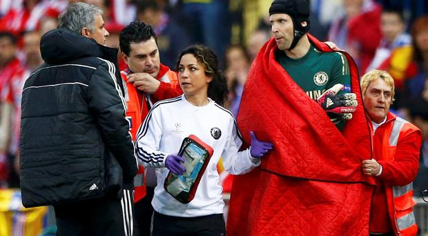 Chelsea's goal keeper Petr Cech walks past his manager Jose Mourihno as he is escorted off the pitch by the team doctor