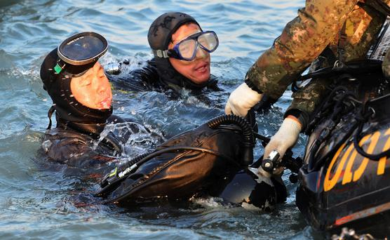 Divers look for people believed to have been trapped in the sunken ferry Sewol in the water off the southern coast near Jindo, south of Seoul, South Korea