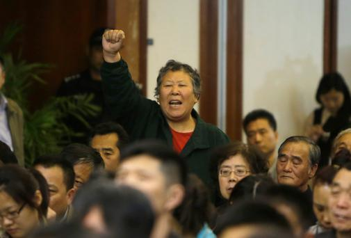 A relative of a passenger aboard Malaysia Airlines flight MH370 gestures as she shouts at Malaysian representatives during a briefing at Lido Hotel in Beijing earlier this week