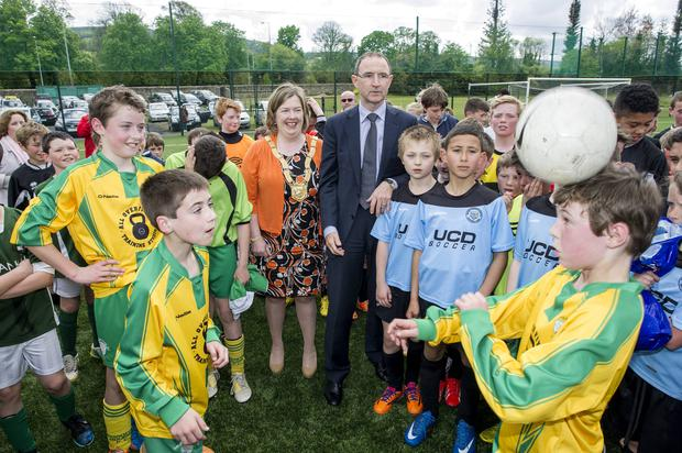 Young soccer players from Broadford Rovers and Mount Merrion with Ireland manager Martin O'Neill and Carrie Smyth at the official opening of the all-weather pitch at Marley Park, Rathfarnham, in Dublin yesterday
