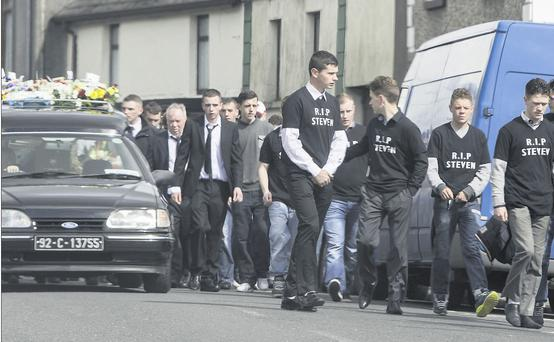 Sorrow: Mourners walk beside the funeral cortege as Steven Carney is laid to rest.