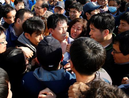 Angry family members of missing passengers onboard the capsized Sewol ferry surround and tug at the shirt of a South Korean coast guard official (C, in blue) and a government official (2nd R) as they demand for faster and more efficient rescue work at a port where many family members are waiting for news from the search and rescue team in Jindo April 24, 2014