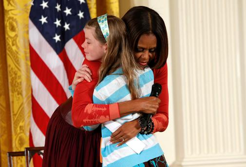 First lady Michelle Obama hugs Charlotte Bell (10), who gave the first lady her father's resume and said he had been out of work for three years, as Michelle Obama was speaking with children of Executive Office employees at the White House's annual Take Our Daughters and Sons to Work Day in Washington yesterday. Reuters