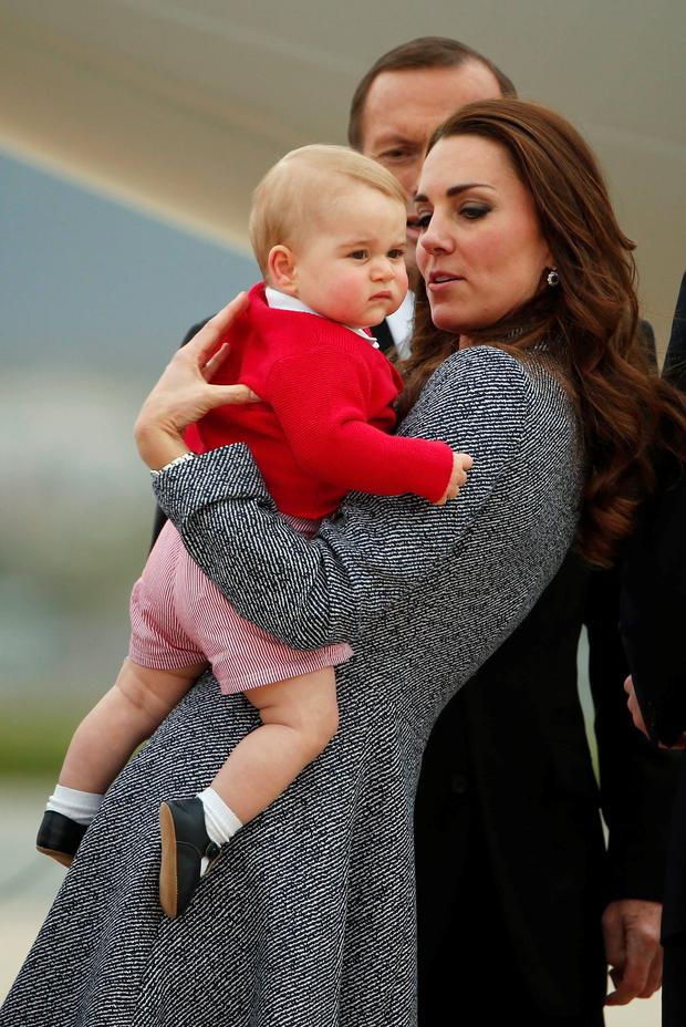 Kate Middleton holds her son Prince George with Australian Prime Minister Tony Abbott behind them, as they prepare to board a plane with her husband Prince William to depart Canberra April 25, 2014. REUTERS/Phil Noble