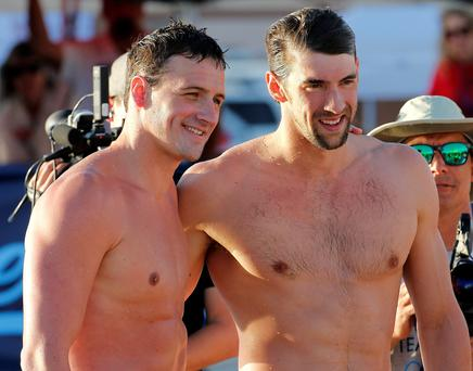 Michael Phelps, right, and Ryan Lochte pose for a photo after competing in the 100-meter butterfly final during the Arena Grand Prix swim meet