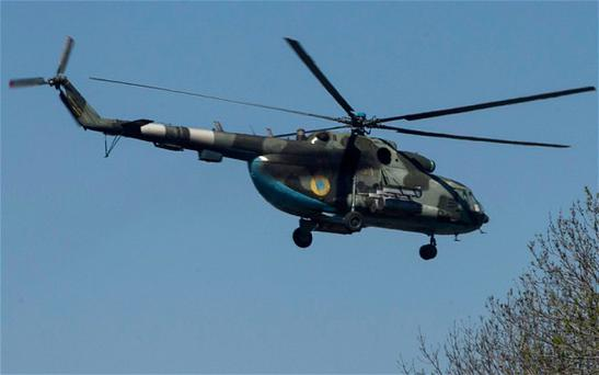 An Ukrainian military helicopter flies near the village of Malinivka, east of Slavyansk Photo: Baz Ratner/Reuters