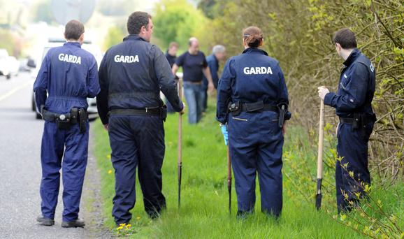 Gardai search an area near a car park over looking Lough Owel, outside Mullingar, Co Westmeath, where a car was found in connection with two missing men from Dublin. Photograph: James Flynn/APX
