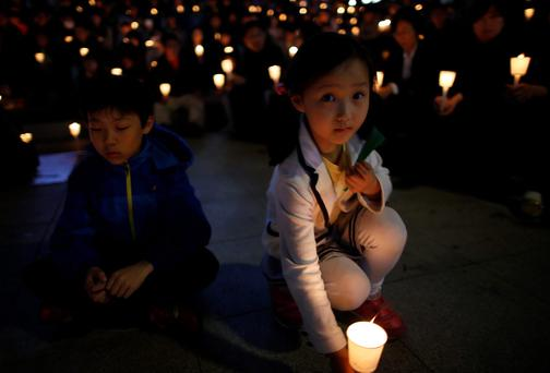 A girl takes part in a candlelight vigil in Ansan, to commemorate the victims of the sunken passenger ship Sewol and to wish for the safe return of missing passengers