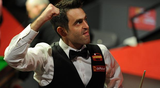 Ronnie O'Sullivan celebrates winning his second round match against Joe Perry during the Dafabet World Snooker Championships at The Crucible, Sheffield.