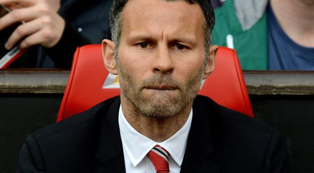 Manchester United's interim manager Ryan Giggs takes his seat before the Barclays Premier League match at Old Trafford, Manchester