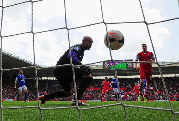 Everton's Tim Howard watches the ball go into the net from teammate Antolín Alcaraz