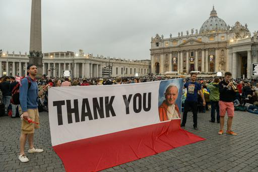 Piilgrims show a banner picturing Pope John Paul II as they gather to Saint Peter's Square