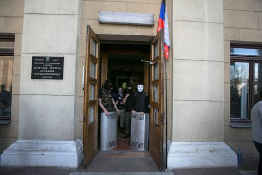 Pro-Russian activists block the entrance to a television station in Donetsk