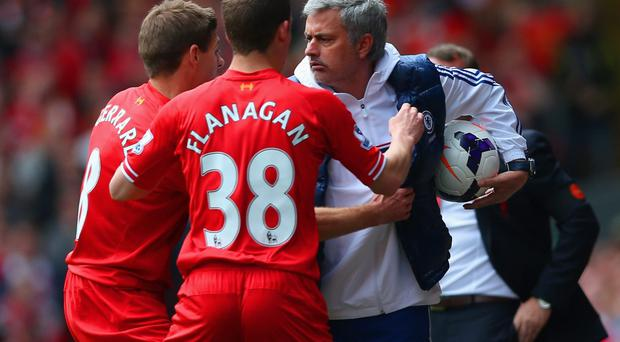 Liverpool's Steven Gerrard and Jon Flanagan have words with Chelsea manager Jose Mourinho as they try to retrieve the ball at Anfield yesterday