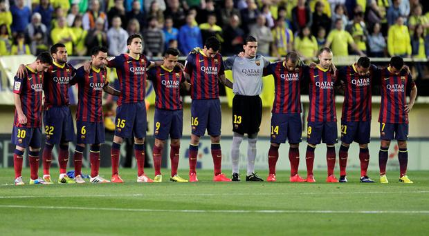Barcelona's players observe a minute of silence for their former coach Tito Vilanova before their match against Villarreal at the Madrigal