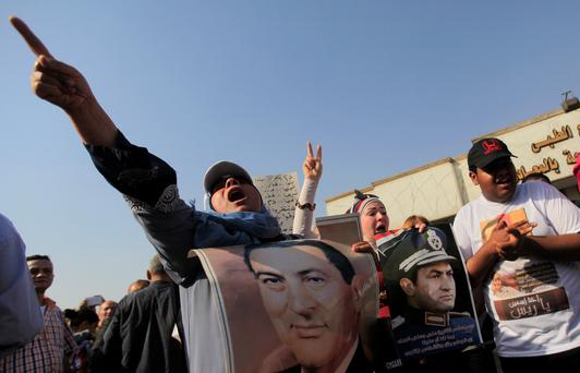 Supporters of former Egyptian president Hosni Mubarak hold his posters while shouting slogans against members of the Muslim Brotherhood during a celebration of the 32nd anniversary of the liberation of Sinai in front of Maadi military hospital on the outskirts of Cairo April 25, 2014.