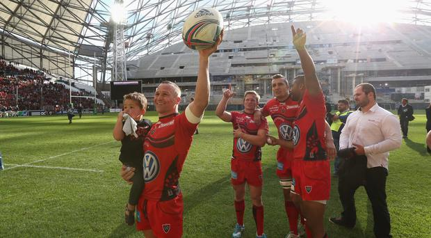 Matt Giteau (L) of Toulon leads the celebrations after their victory over Munster in front of a barren stand at the Stade Velodrome