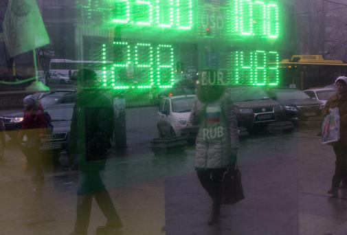 Pedestrians are reflected in the window of a foreign currency exchange store advertising its rates in Kiev, Ukraine. Stress tests will assess the strength of Europe's banking system and its ability to overcome real-world tensions like those in Ukraine.