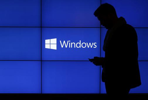 A visitor check his smartphone in front of a Windows display at a Microsoft Corp. news conference ahead of the Mobile World Congress in Barcelona, Spain, on Sunday, Feb. 23, 2014. Photographer: Simon Dawson/Bloomberg