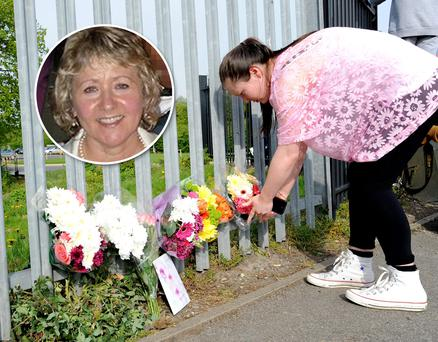 A woman lays flowers outside Corpus Christi Catholic College, Neville Road, Leeds, where a 15-year-old boy has been arrested after a woman teacher was stabbed to death at the school. Photo: PA