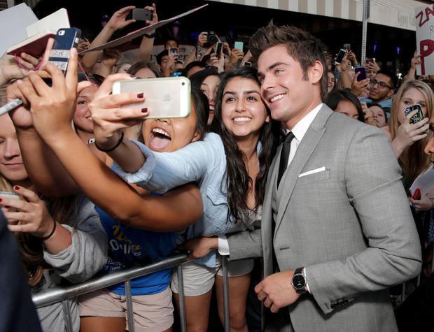 Zac Efron poses for a photo with a fan as he arrives at the world premiere of