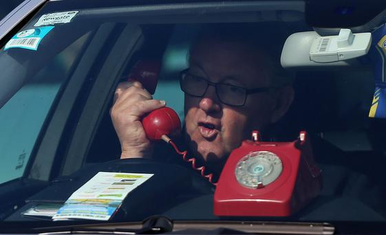A man uses a phone in his car in Dublin as a protest. Photo: Niall Carson/PA Wire