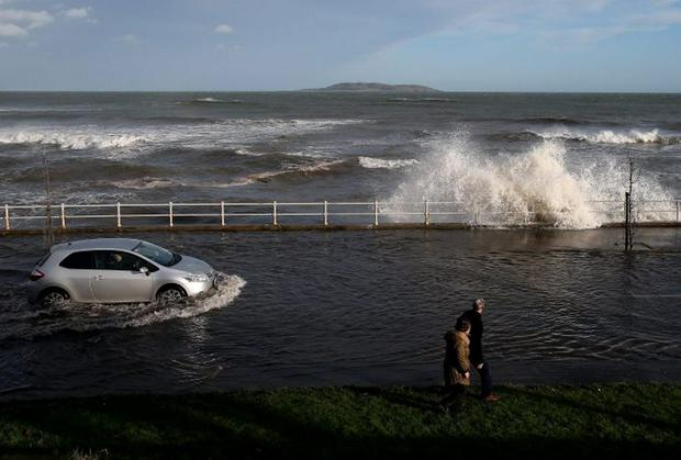 A car attempts to drive through floods caused by waves crashing onto the Coast Road in Malahide, Dublin. Brian Lawless/PA Wire