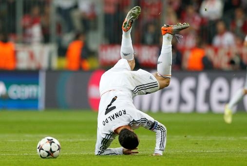 Real's Cristiano Ronaldo is upside down after a foul by Bayern's Dante