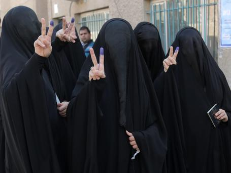Iraqi women give the victory signs while showing their inked fingers after casting votes at a polling center in Baghdad, Iraq. AP Photo/Khalid Mohammed
