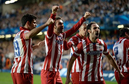 Atletico Madrid's Adrian Lopez (centre) celebrates with his team-mates after scoring his side's first goal during the UEFA Champions League match at Stamford Bridge.