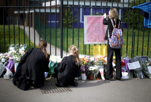 Pupils place tributes to murdered teacher Anne Maguire outside Corpus Christi Catholic College in Neville Road in Leeds, England