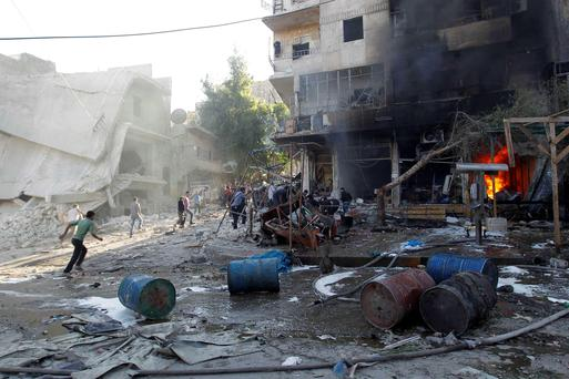Residents run after, according to activists, two barrel bombs were thrown by forces loyal to Syria's president Bashar Al-Assad in Hellok neighbourhood of Aleppo