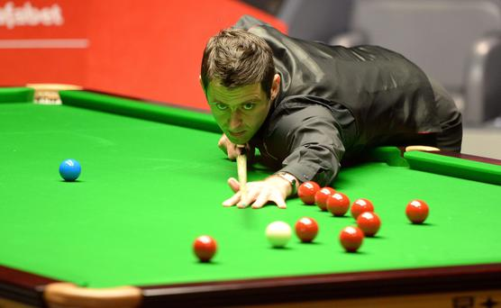 Ronnie O'Sullivan plays a shot against Barry Hawkins, during the semi final of The Dafabet World Snooker Championships at The Crucible