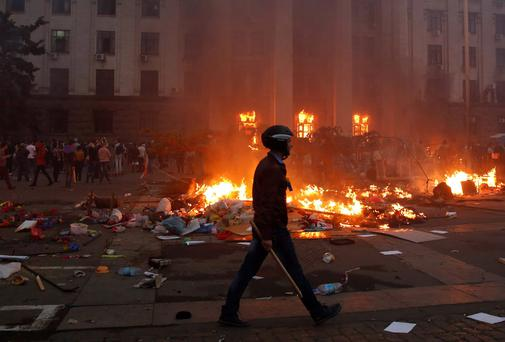 A protester walks past a burning tent camp and a fire in the trade union building in Odessa. At least 38 people were killed in a fire on Friday in the trade union building in the centre of Ukraine's southern port city of Odessa, regional police said. Reuters