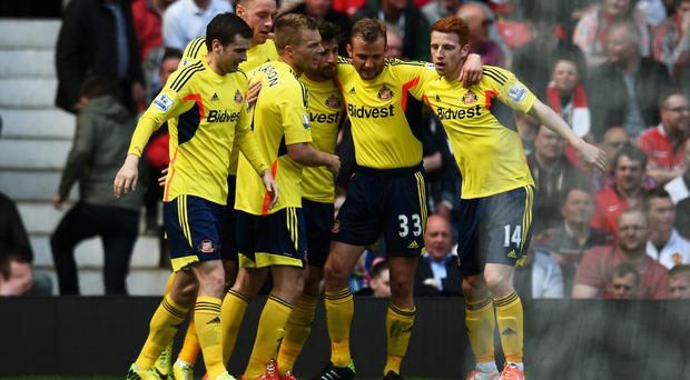 Sebastian Larsson (3rd L) of Sunderland is congratulated by teammates after scoring the winner at Old Trafford