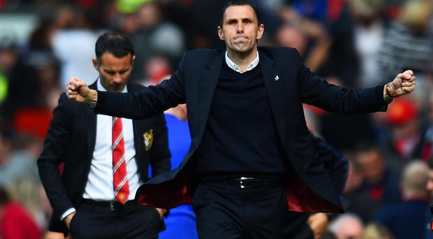 Gustavo Poyet the Sunderland manager celebrates his team's 1-0 victory as a dejected Ryan Giggs the Manchester United interim manager walks behind