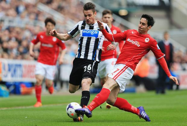 Mathieu Debuchy of Newcastle United is tackled by Peter Whittingham of Cardiff City